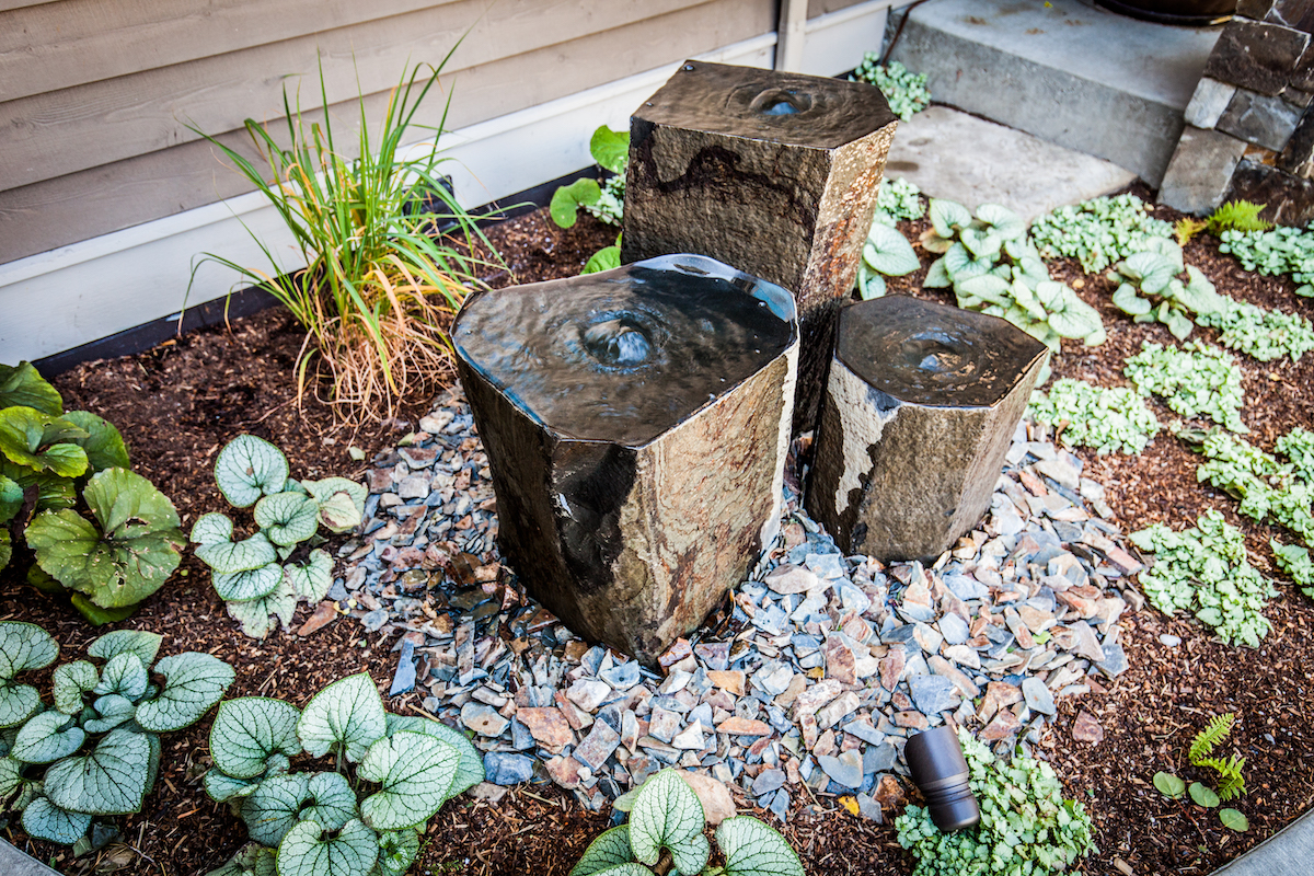 Small stone water feature with landscaping
